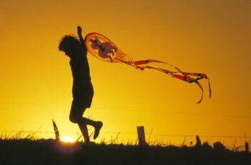 870436Child-Flying-a-Kite-at-Sunset